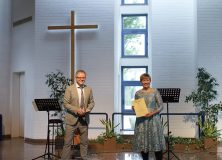 Pastor Hendrik Kissel überreicht Maike Böhl die Ordination-Urkunde